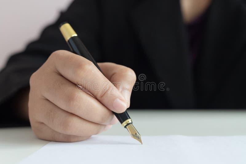 Mano ascendente cercana del tiro de la mujer de negocios usando la pluma a escribir en la profundidad baja del foco selecto del L imagenes de archivo
