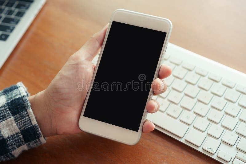 Mano ascendente cercana usando fondo del escritorio del smartphone en oficina A mano llevar a cabo la exhibición en blanco del sm fotos de archivo