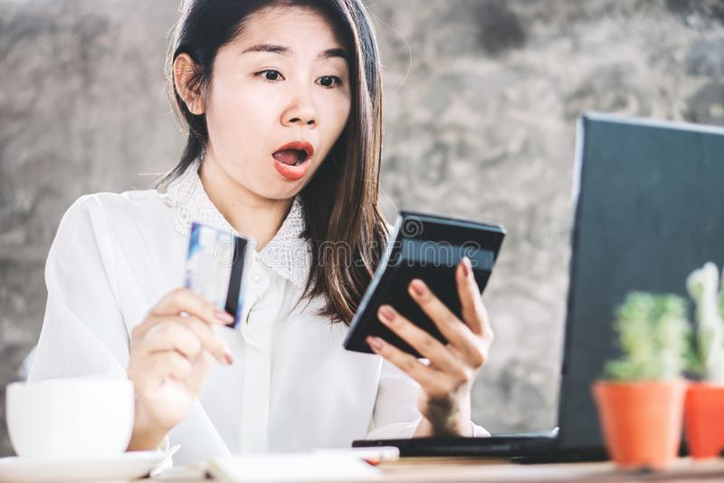 Mano asiática chocada de la mujer que cuenta costos en la calculadora que tiene problema con la tarjeta de crédito imagenes de archivo