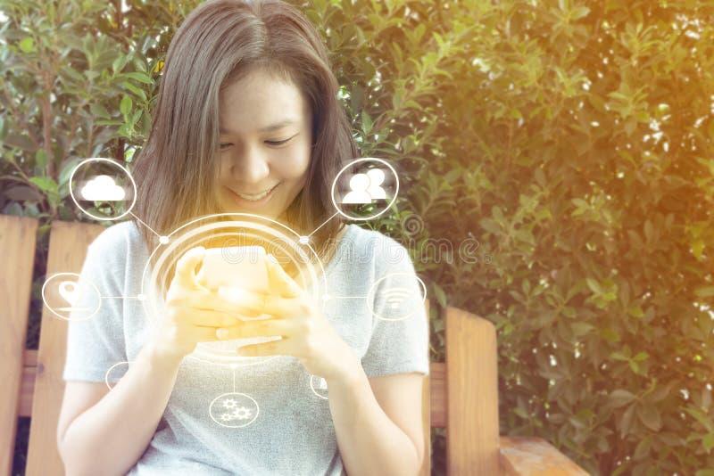 Mano asiática de la mujer usando el teléfono móvil en jardín con el espacio de la copia, I fotos de archivo