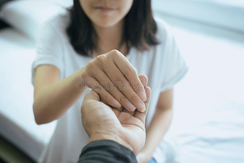 Mano asiática de la tenencia del amante de los pares a animar en tiempos de problemas de la decepción o de la vida junto, concept fotos de archivo libres de regalías