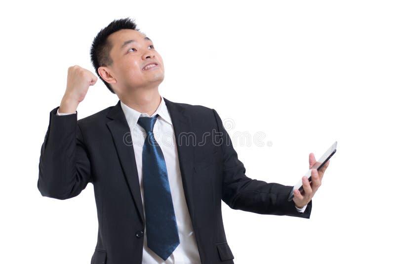 Mano asiática moderna del hombre de negocios que celebra la celebración digital de la tableta acertada Hombre de negocios feliz y fotografía de archivo