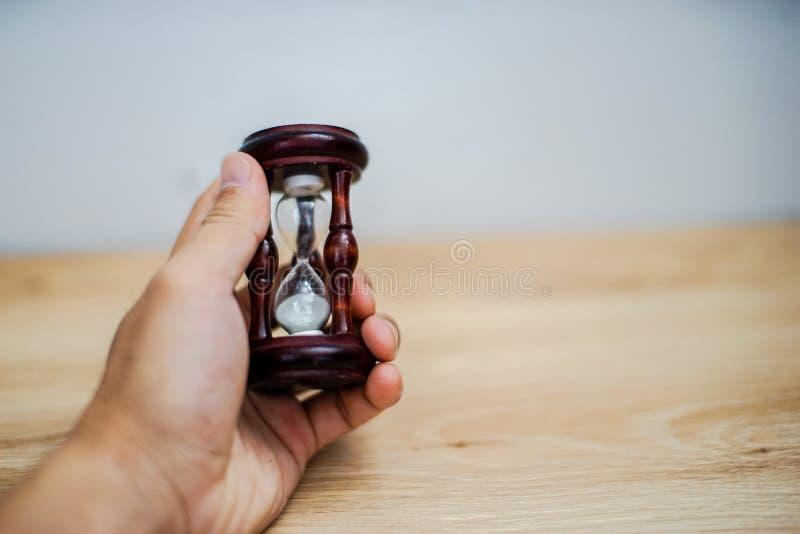 Mano asiática que sostiene un reloj de arena en el fondo blanco fotos de archivo