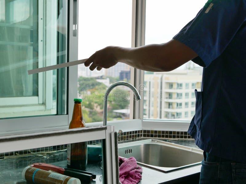 Mano asiatica del tecnico che lavora manualmente ad un'installazione di una finestra di scivolamento immagini stock libere da diritti