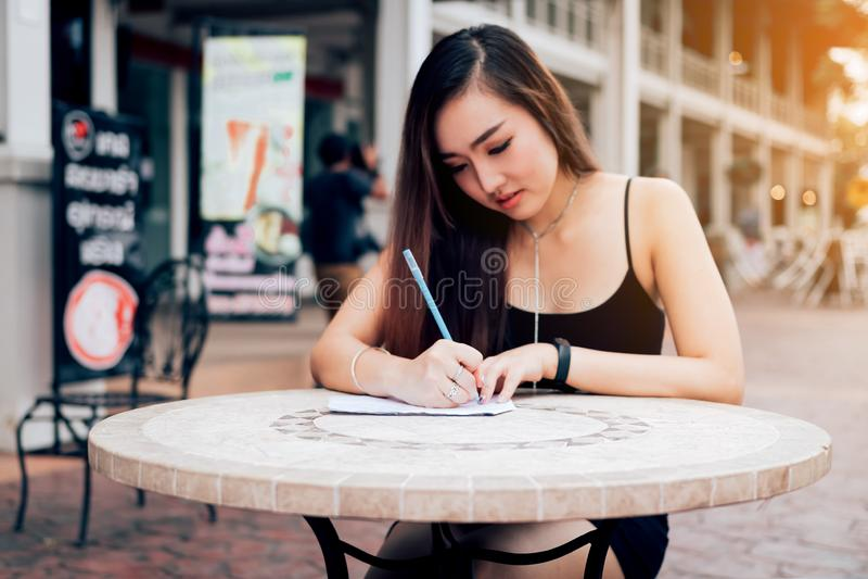 Mano asiatica della donna che controlla la lista di acquisto sullo scrittorio al outle esterno fotografia stock