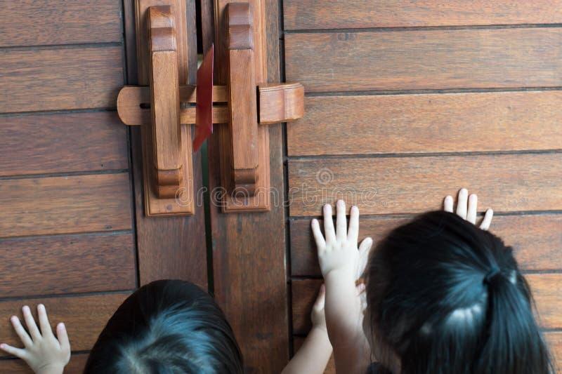Mano asiatica di due una piccola ragazze ha messo sopra la porta di legno con la busta rossa fotografie stock libere da diritti