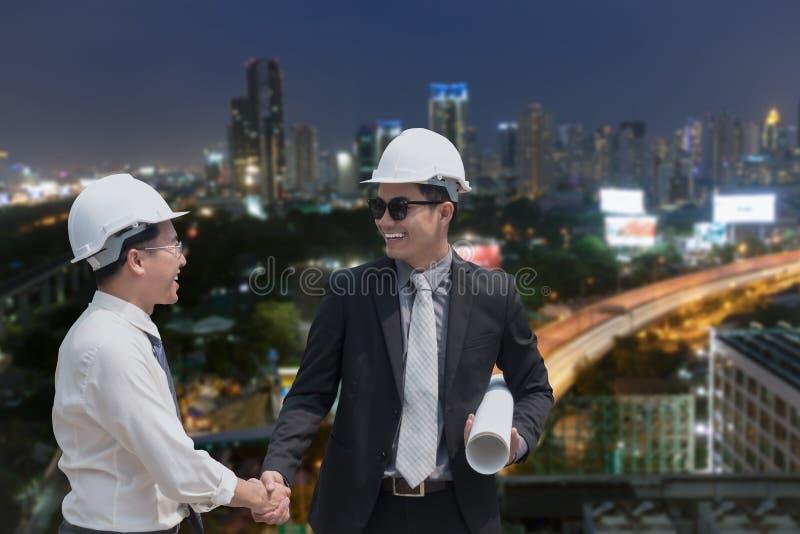 Mano asiatica di scossa dell'uomo d'affari con il professiona dell'architetto dell'ingegnere immagini stock libere da diritti