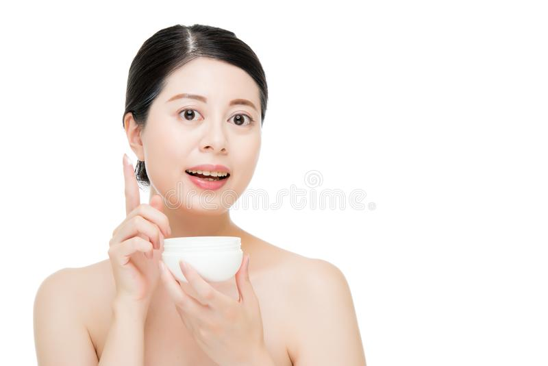 Mano asiatica di uso della donna di bellezza che applica prodotto facciale immagine stock