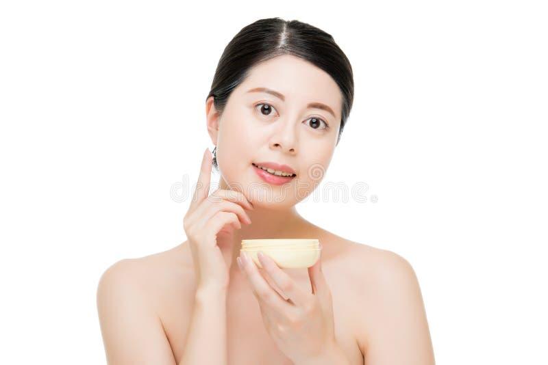 Mano asiatica di uso della donna di bellezza che applica prodotto facciale fotografie stock libere da diritti