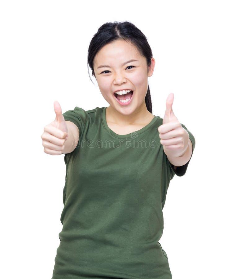 Mano asiatica emozionante della donna due con il pollice su fotografie stock