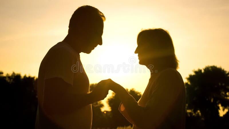 Mano atenta de la esposa de la tenencia del marido, fecha romántica en la puesta del sol en parque, cuidado foto de archivo libre de regalías