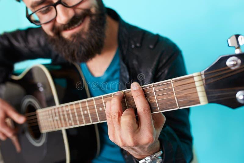 Mano barbuda del hombre del inconformista que juega en la guitarra acústica fotos de archivo