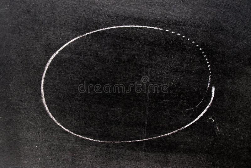 Mano bianca del gesso che assorbe forma del cerchio sul fondo della lavagna immagini stock libere da diritti