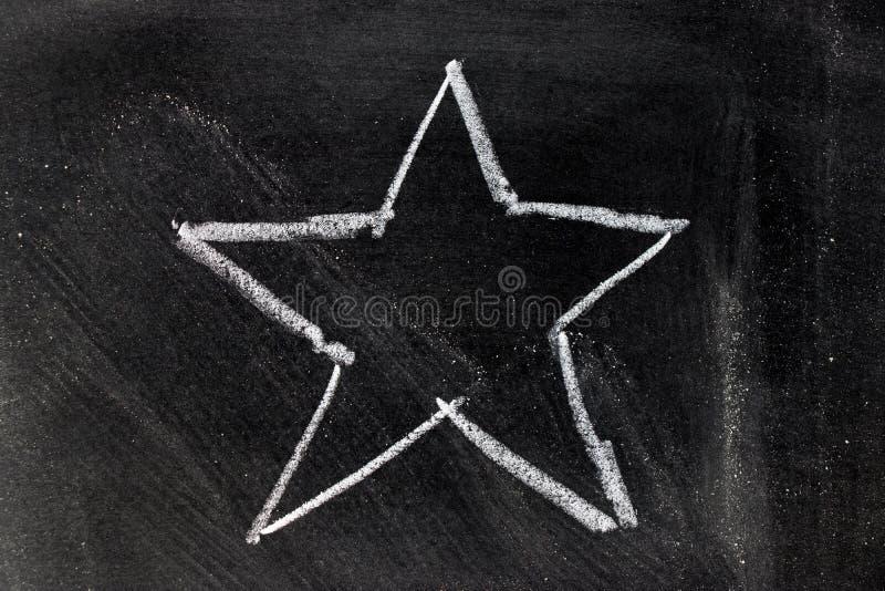 Mano bianca del gesso che assorbe forma della stella sulla lavagna immagine stock libera da diritti
