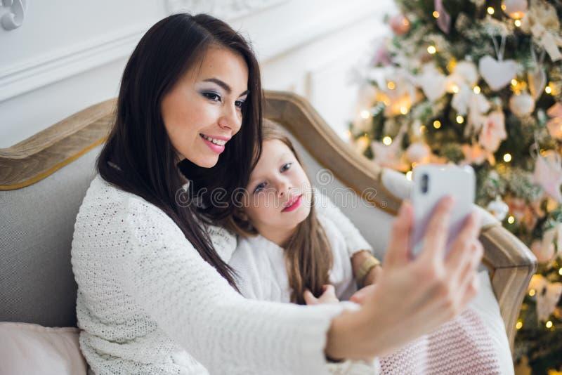 Mano bien arreglada de una mujer que sostiene un teléfono que toma un selfie con su hija, niña imagenes de archivo