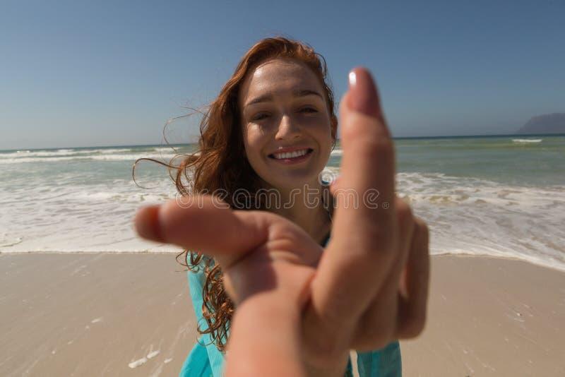 Mano caucásica joven de la mujer que alcanza hacia la cámara en la playa imagen de archivo
