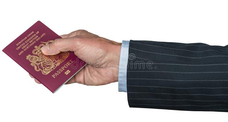 Mano caucásica mayor que sostiene el pasaporte BRITÁNICO imagen de archivo libre de regalías