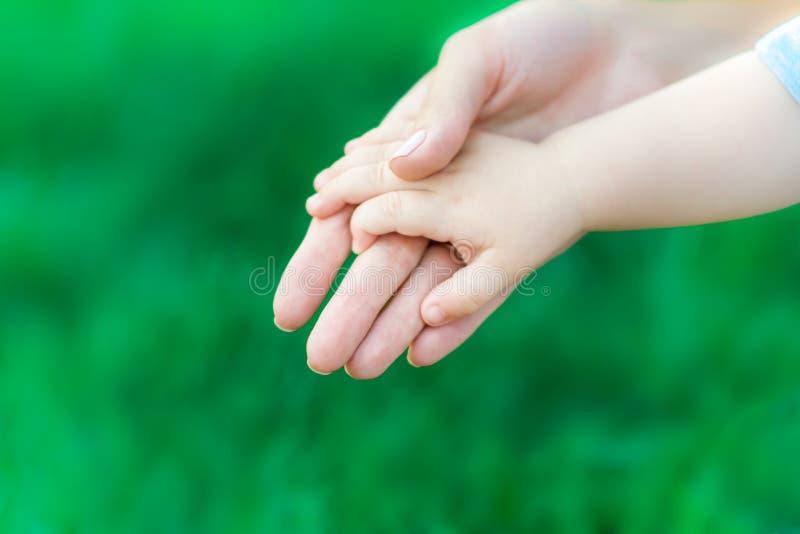 Mano caucasica della tenuta della madre del neonato sul fondo dell'erba verde Il concetto di amore materno, di cura e di salute fotografia stock libera da diritti