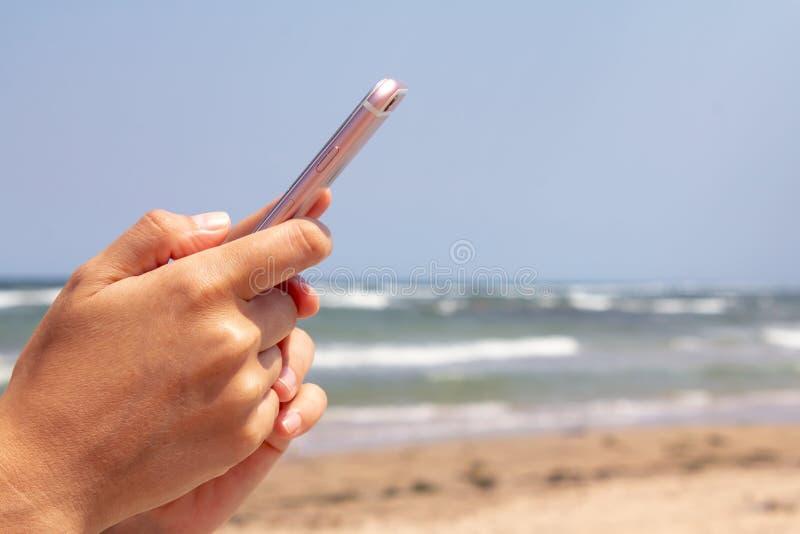 Mano cercana de la mujer que manda un SMS en el fondo del mar en la playa imagen de archivo libre de regalías
