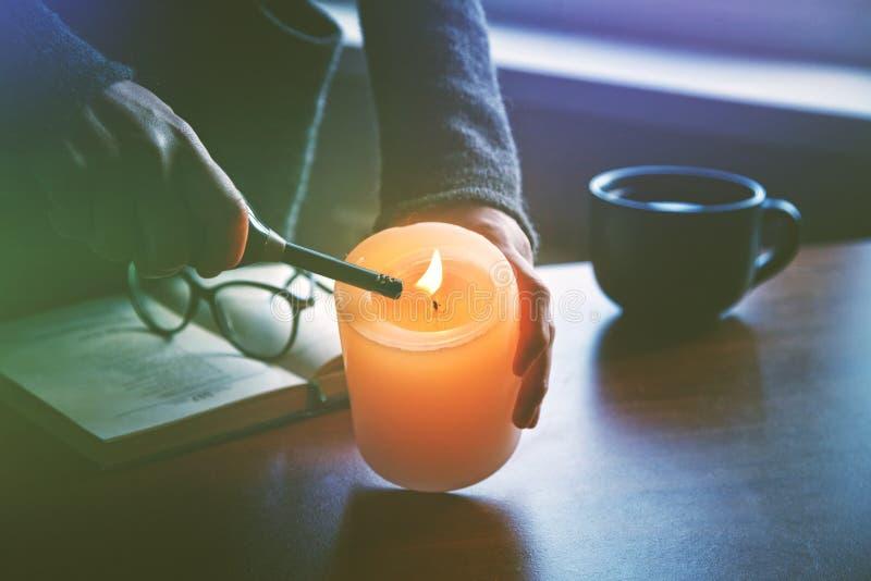 Mano che accende candela prima del libro di lettura fotografie stock