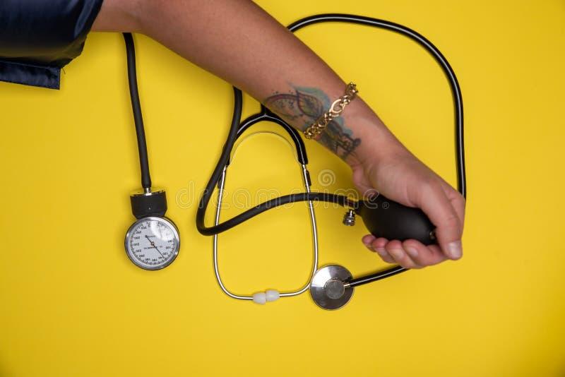 Mano che controllano pressione sanguigna e stetoscopio accantonato fotografia stock