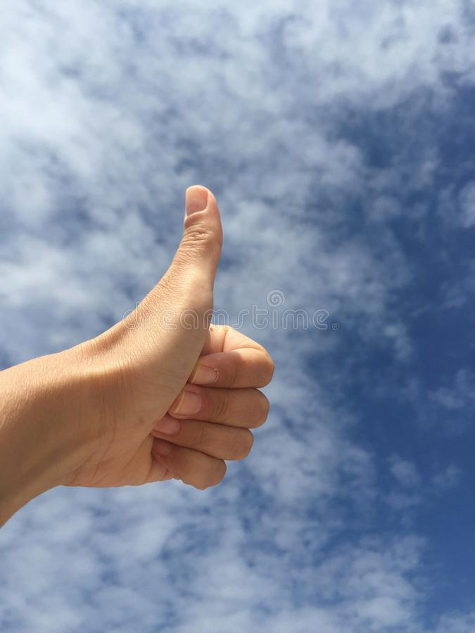 Mano che fa segno GIUSTO contro il cielo blu fotografia stock