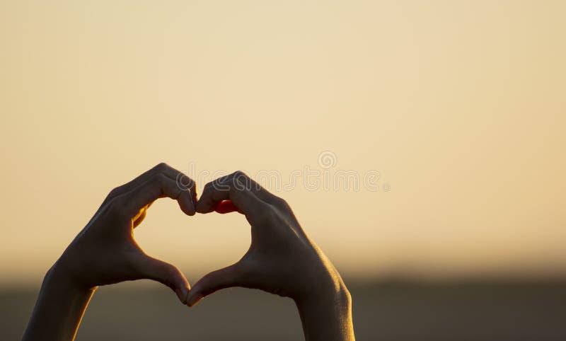Mano che fa una forma del cuore di amore fotografia stock libera da diritti