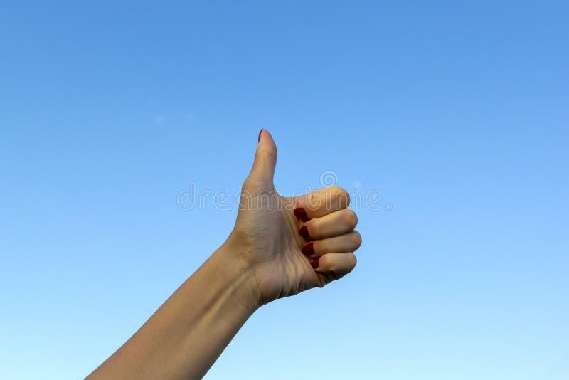 Mano che gesturing i pollici sulla mostra buona o sull'approvazione sul fondo del cielo blu immagini stock