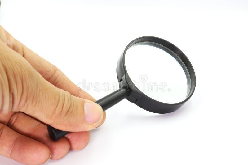 Mano che giudica il vetro di Magniflying isolato su fondo bianco fotografia stock libera da diritti