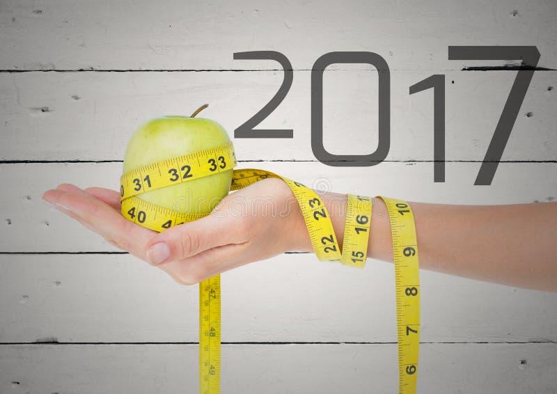 Mano che giudica mela verde avvolta con nastro adesivo di misurazione contro 2017 fotografia stock libera da diritti