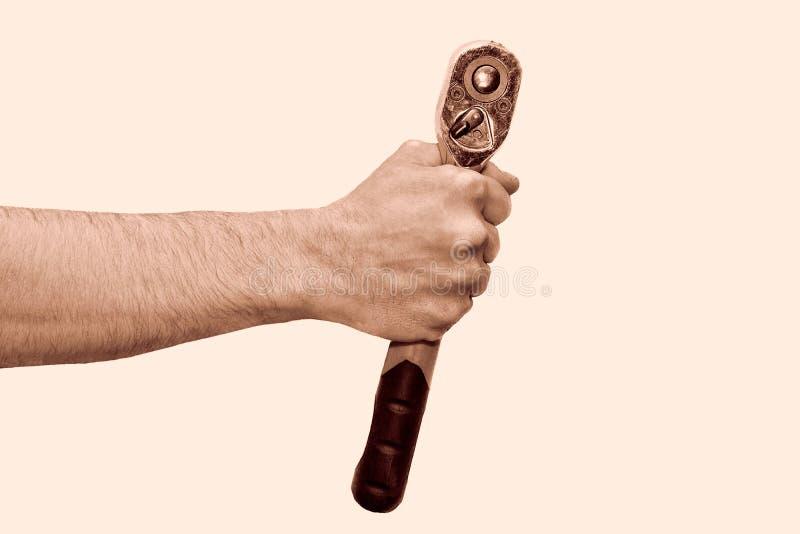 Mano che giudica una chiave a cricchetto isolata su bianco Strumento della chiave della tenuta della mano del meccanico a disposi fotografia stock libera da diritti