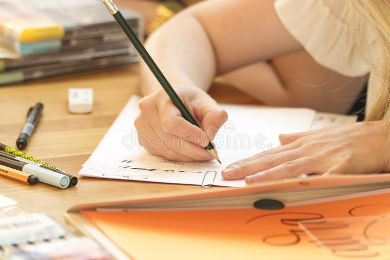 Mano che impara iscrizione nella classe con la matita nera e Libro Bianco e caos in scrittorio immagini stock libere da diritti