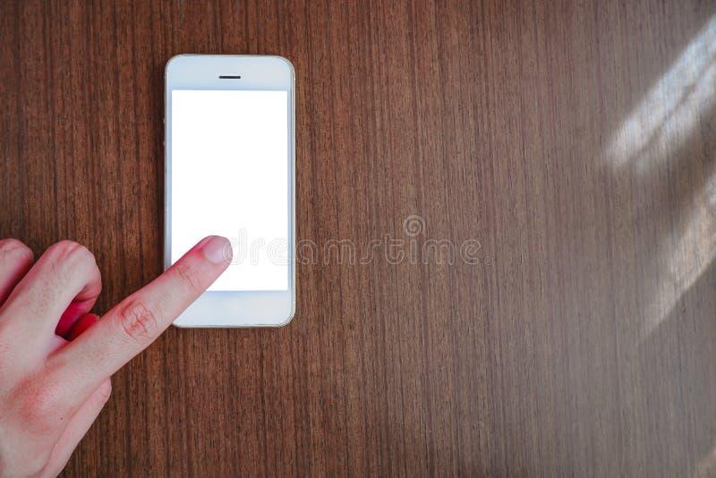 Mano che indica dito allo smartphone con lo schermo bianco immagine stock
