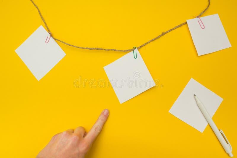 Mano che indica l'attaccatura di carte per appunti su una corda, spazio vuoto per testo immagini stock libere da diritti