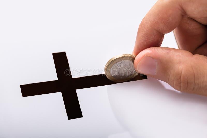 Mano che inserisce moneta nella scanalatura della croce fotografia stock libera da diritti