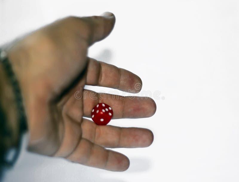 Mano che lancia un dado rosso, oltre al classico gioco di dadi ci sono molti altri giochi che usano il dado per essere ab fotografie stock libere da diritti