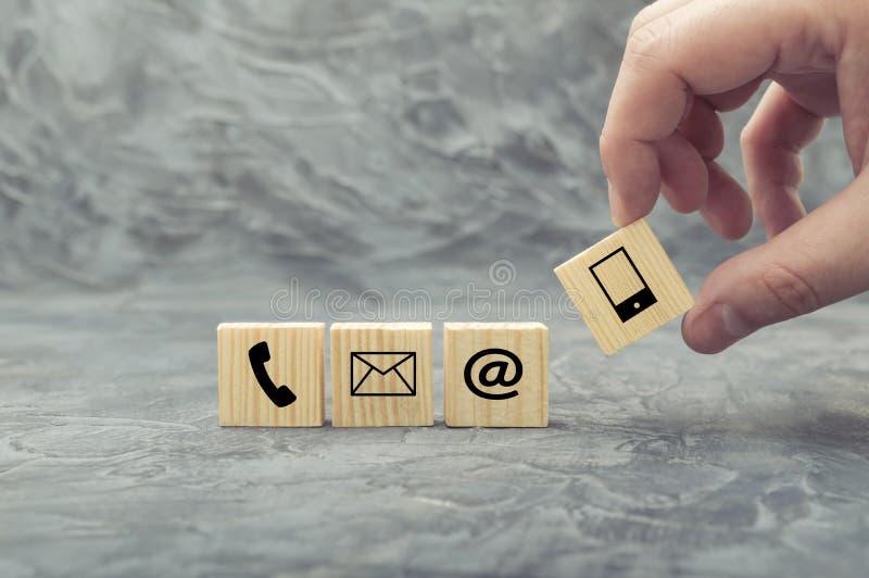 Mano che mette il cubo di legno del blocco con il telefono, la posta, l'indirizzo ed il telefono cellulare di simbolo fotografie stock libere da diritti