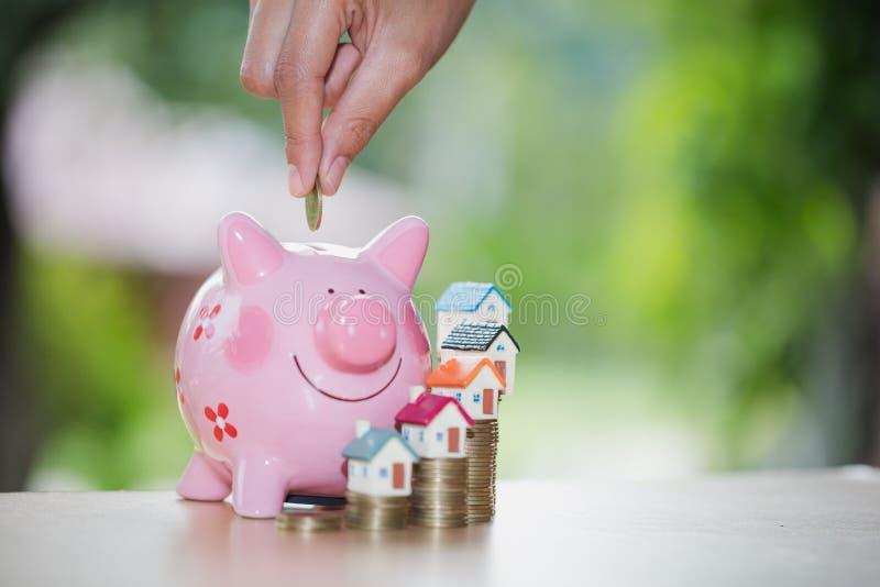 Mano che mette moneta nel porcellino salvadanaio, soldi di risparmio per comprare una casa, fotografie stock