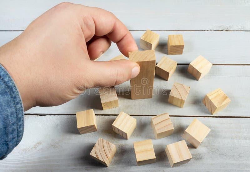 Mano che mette una foto di legno di concetto del blocco fotografie stock libere da diritti