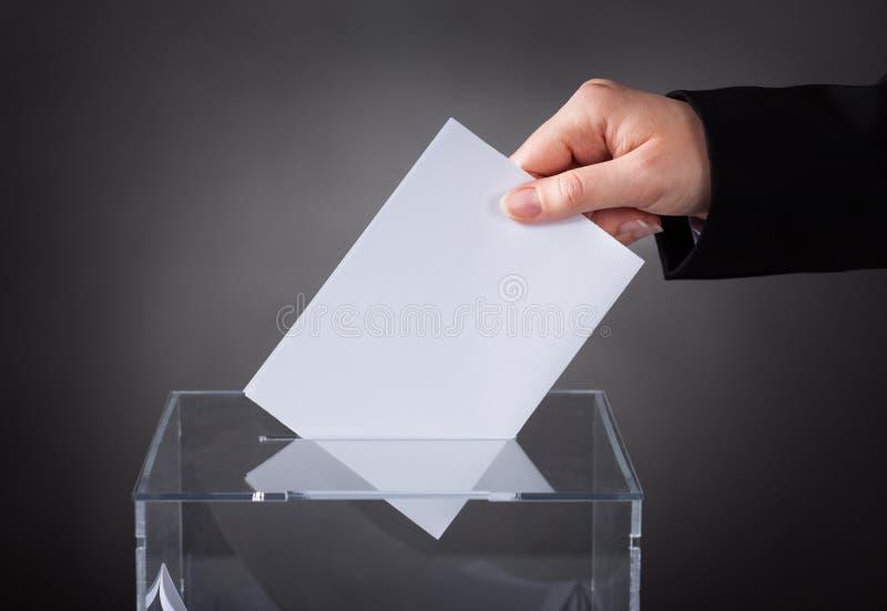 Mano che mette voto in scatola fotografie stock