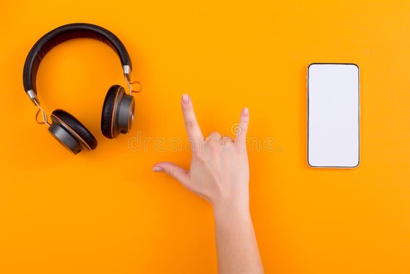 Mano che mostra il segno della roccia con il telefono e le cuffie su fondo arancio immagine stock libera da diritti