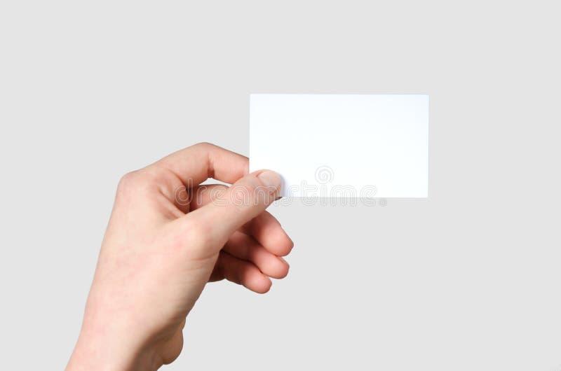 Mano che mostra un biglietto da visita in bianco immagini stock