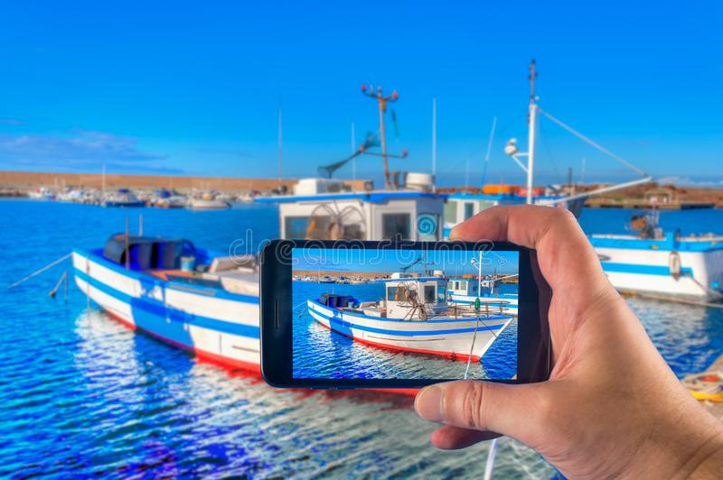 Mano che prende immagine con uno smartphone di un peschereccio nel porto di estate fotografia stock