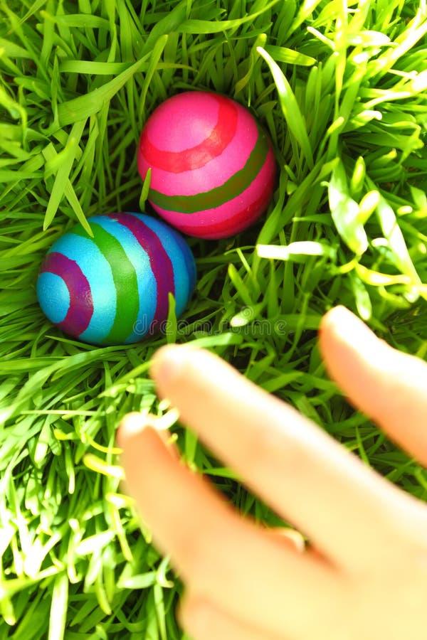 Mano che raggiunge per le uova di Pasqua fotografia stock