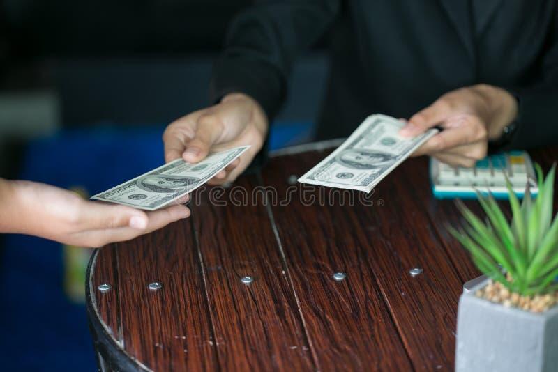 Mano che riscuote fondi, dollari americani, dall'uomo di affari, uomo d'affari che dà soldi al suo partner mentre stipulando cont fotografia stock