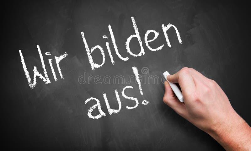 """Mano che scrive """"formiamo la gente! """"in tedesco immagine stock"""