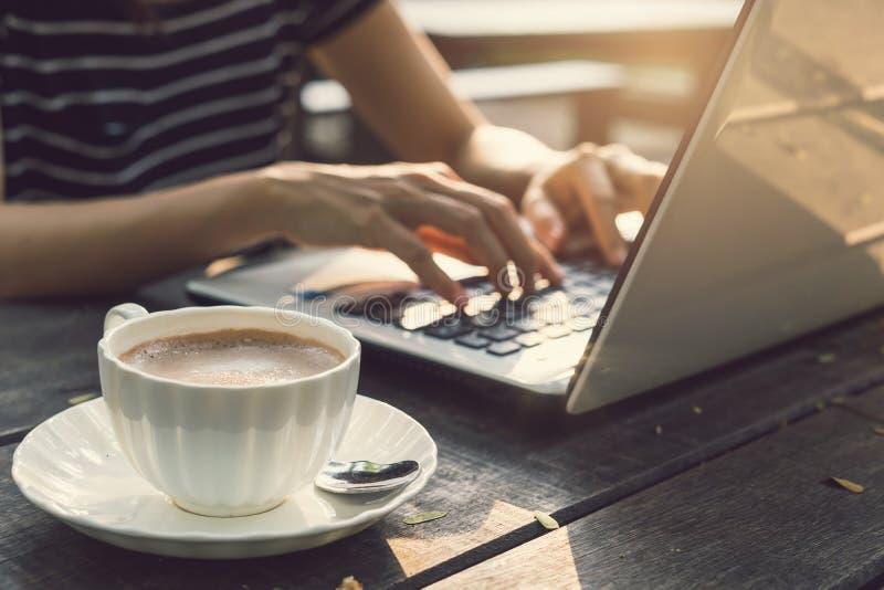 Mano che scrive sul computer portatile della portachiave con la tazza di caffè fotografia stock libera da diritti