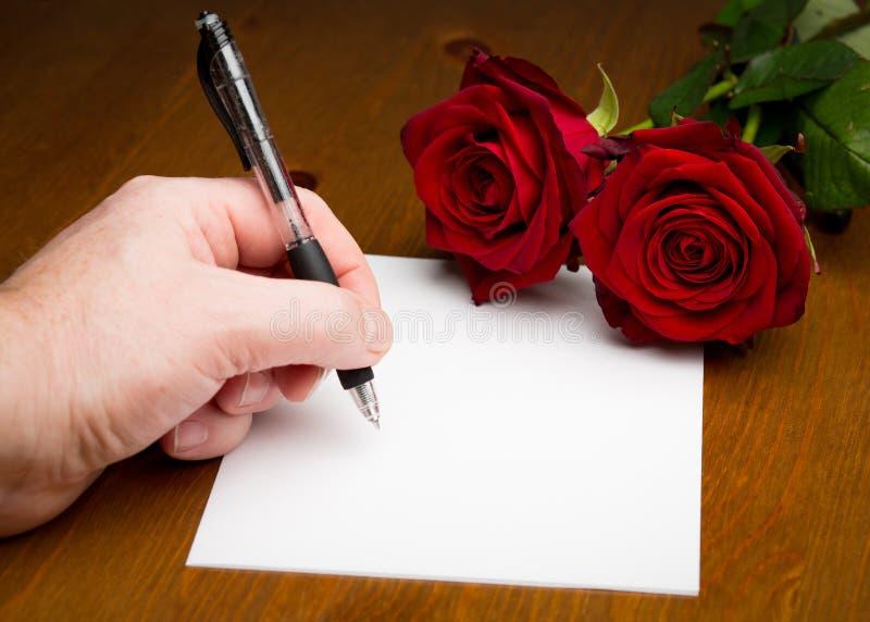 Mano che scrive un amore Valentine Letter With Roses immagine stock libera da diritti