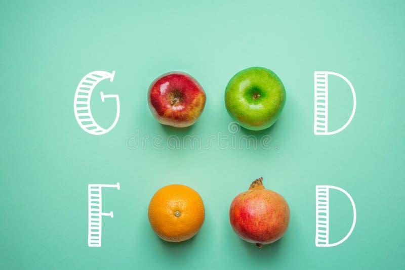 Mano che segna buon alimento con lettere sul fondo del turchese con il melograno rosso verde arancio delle mele di frutti Vegano  immagine stock libera da diritti