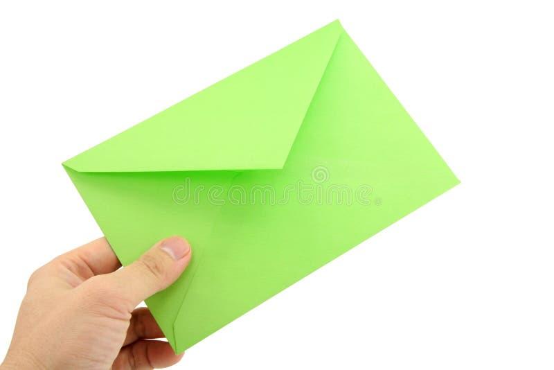 Mano che tiene busta verde fotografia stock libera da diritti